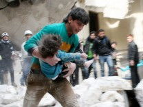 A man carries an injured child that was taken out from under debris at a site after what activists said was shelling by forces loyal to Syria's President Bashar al-Assad in Al-Sukkari neighbourhood in Aleppo