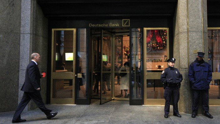 A New York City Police Officer stands beside a security officer at the entrance of a Deutsche Bank office in New York in this file photo