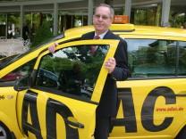 ADAC-Präsident Peter Meyer vor einem Straßenwacht-Fahrzeug.