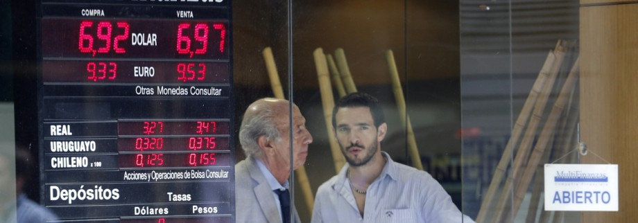 Two men stand next to a exchange billboard showing the official U.S dollar rate to Argentine pesos in Buenos Aires