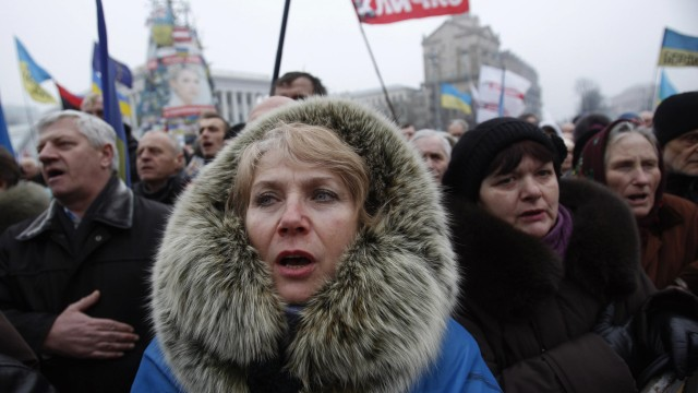 People sing the Ukrainian national anthem during an anti-government rally in Kiev