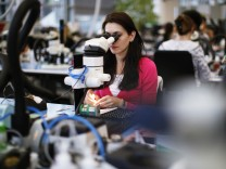 File photo of an employee working in production facility of Phonak hearing devices of Swiss hearing aid maker Sonova in Staefa