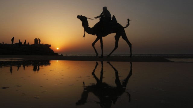 A Palestinian man rides a camel during sunset on the beach of Gaza City