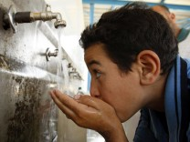 A Palestinian youth drinks water from a public tap in Khan Younis in Gaza