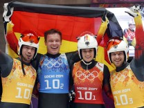 Germany's Arlt, Loch, Geisenberger and Wendt pose with their national flag during luge team relay competition at 2014 Sochi Winter Olympics