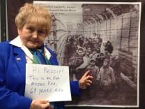 Eva Mozes Kor vor einem Plakat. Darauf zu sehen ist die Befreiung von Auschwitz. In der ersten Reihe steht Eva mit ihrer Zwillingsschwester Miriam