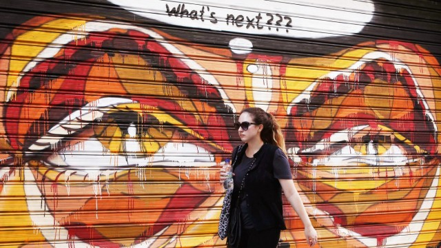 A woman walks in front of a graffiti painted on a shop shutter, in Athens