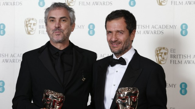 Director Alfonso Cuaron and producer David Heyman celebrate after winning Outstanding British Film for 'Gravity' in London