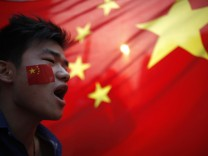 A demonstrator shouts slogans during a protest in front of a Chinese national flag in Shanghai