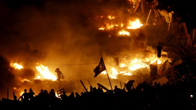 Anti-government protesters stand behind burning barricades in Kiev's Independence Square