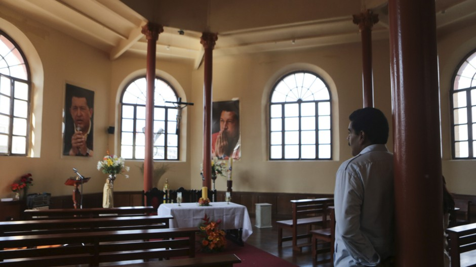 Acting Venezuelan President Maduro and his wife stand in a chapel with posters of late President Chavez in Caracas