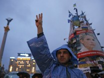 An anti-government protester gestures during a rally in Independence Square, with a poster displaying Ukrainian opposition leader Tymoshenko seen in the background, in central Kiev