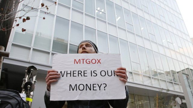 Burges holds a placard to protest against Mt. Gox in Tokyo