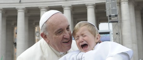 Pope Francis blesses a baby dressed as the Pope as he arrives to lead his Wednesday general audience at the Vatican