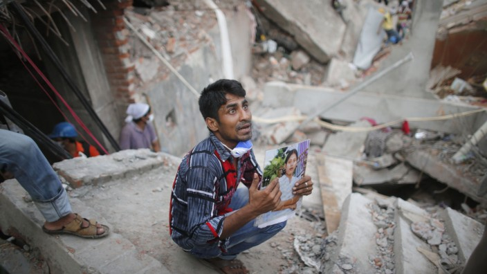 Relative holds picture of a garment worker in front of the rubble of the collapsed Rana Plaza building, in Savar