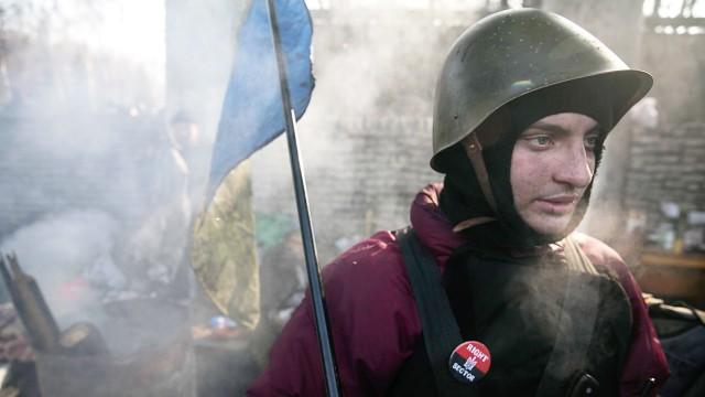 A Right Sector anti-Yanukovich protester guards a barricade in central Kiev