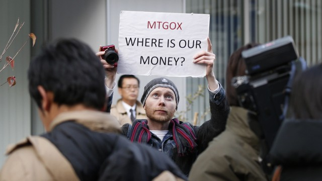 Burges, a self-styled cryptocurrency trader and former software engineer from London, holds up a placard to protest against Mt. Gox in Tokyo