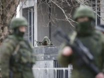 Armed men patrol around the regional parliament building in the Crimean city of Simferopol