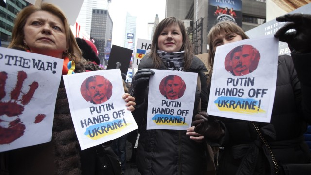 Women hold up signsduring a protest march in support of peace in the Ukraine in Times Square in New York