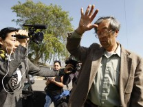 A man widely believed to be Bitcoin currency founder Satoshi Nakamoto is surrounded by reporters as he leaves his home in Temple City, California