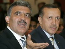Turkey's Foreign Minister Abdullah Gul gestures as he is flanked by Prime Minister Tayyip Erdogan before a news conference with Iraq's PM Nuri al-Maliki in Ankara