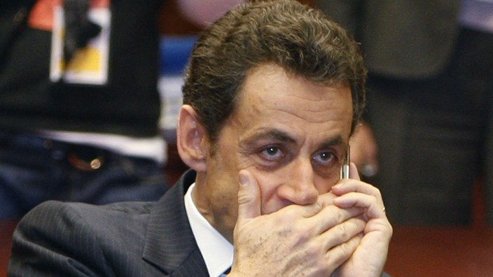 File photo of French President Sarkozy who makes a phone call at the start of a meeting on the second day of a European Union leaders summit in Brussels