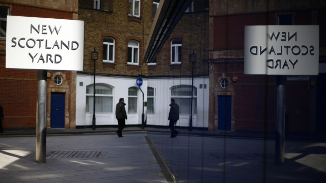 The sign outside New Scotland Yard is reflected outside the headquarters of the Metropolitan Police in central London