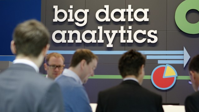 People stand in front of a big data analytics logo at the booth of IBM during preparations for the CeBIT trade fair in Hanover