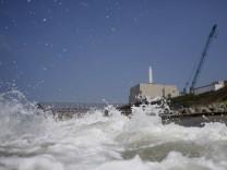 Chubu Electric Power Co.'s Hamaoka Nuclear Power Station is seen behind waves at a beach in Omaezaki