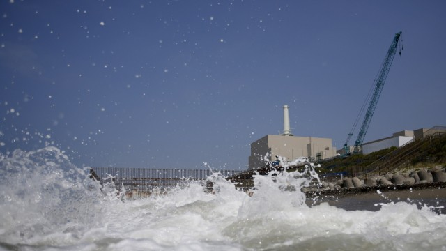 Chubu Electric Power Co.'s Hamaoka Nuclear Power Station is seen behind waves at a beach in Omaezaki