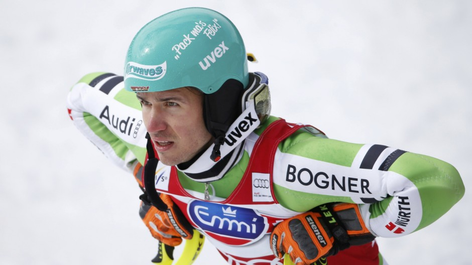 Runner up Neureuther of Germany watches Hirscher of Austria winning the race and the overall slalom and the World Cup trophy at the FIS Alpine Skiing World Cup Finals in Lenzerheide