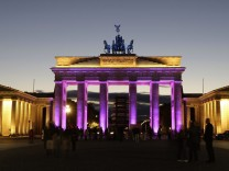 Visitors pass illuminated Brandenburger Tor gate during light rehearsal in Berlin