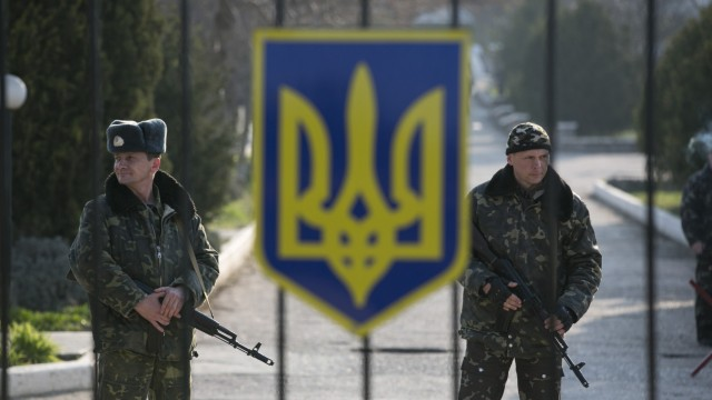 Ukrainian servicemen stand guard at the entrance to a base in the village of Lyubimovka