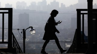 A woman uses her phone while walking on a hazy day in Seoul