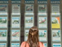 Frau vor Immobilengeschäft