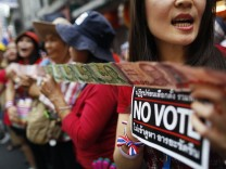 Anti-government protesters hold 'No Vote' stickers and Thai baht banknotes to donate to leader during march in Bangkok