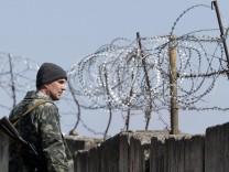 A Ukrainian serviceman stands guard at a Ukrainian military base in the Crimean town of Belbek