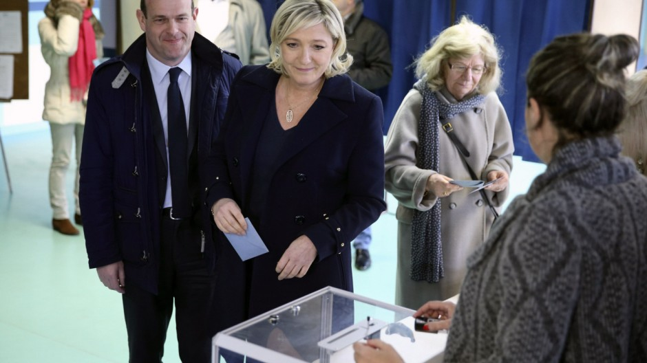 France's far-right National Front political party leader Marine Le Pen prepares to cast her ballot at a polling station during the first round in the French mayoral elections in Henin Beaumont