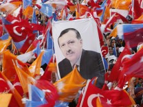 Supporters hold up a portrait of Turkey's PM Erdogan while waving Turkish and AKP flags during an election rally in Istanbul