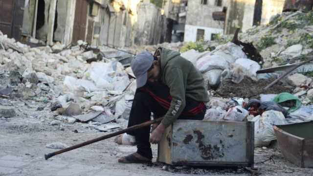An injured boy sits in front of the rubble of damaged buildings in the old city of Aleppo