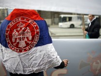 A man wearing Serbian flag attends an anti-European Union protest in Belgrade