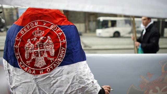 A man wearing Serbian flag attends an anti-European Union protest in Belgrade