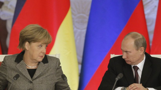 File photo of Russian President Putin and German Chancellor Merkel answering journalists' questions during a joint news conference in Moscow's Kremlin
