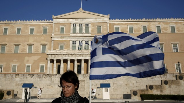 A protester stands in front of the parliament during an anti-government rally outside the parliament in Athens