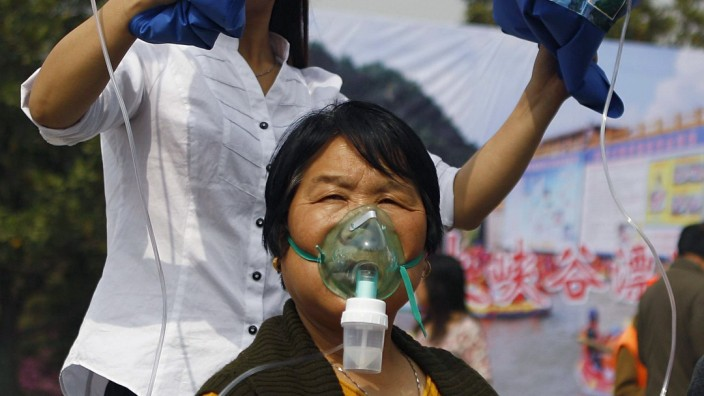 An assistant helps as a woman breathes through a mask connected to a plastic bag with air taken in Laojun Mountain of Luanchuan county, during a promotional event in Zhengzhou