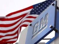 Das Logo von General Motors vor der US-Flagge
