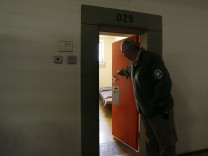 A German prison warden opens the door to one of the single occupant cells at Landsberg County jail
