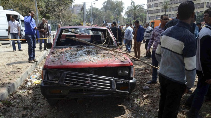 People stand near a damaged car after explosions near Cairo University