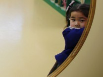 A girl opens the door of a teacher's staff room at the Emporium kindergarten in Koriyama, west of the tsunami-crippled Fukushima Daiichi nuclear power plant, Fukushima prefecture