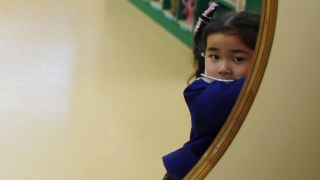 A girl opens the door of a teacher's staff room at the Emporium kindergarten in Koriyama, west of the tsunami-crippled Fukushima Daiichi nuclear power plant, Fukushima prefecture